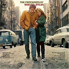 "The Freewheelin' Bob Dylan's album cover. Wearing a brown jacket and blue jeans, a man walks along a snowy street. A woman wearing a long green coat and black pants holds onto his arm and walks alongside him. The words ""The Freewheelin' Bob Dylan"" frame the man's head, and the names of songs contained within the album are listed in small print in the bottom left and right of the image."