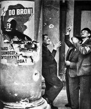 "Siege of Warsaw (1939) - Volunteer fire-fighters watching an air duel over Warsaw. Propaganda poster reads ""To Arms – United, we will defeat the enemy""."