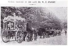 "Black and white press photograph showing the funeral procession. The title is ""Floral tributes to the late Mr. W. F. Stanley"". There are four vehicles shown. From left to right: The hearse horse and carriage, covered in flowers, with an undertaker climbing up onto the carriage. In front of the hearse, there are a horse and carriage, carrying mourners. In front of this carriage are two further horses-and-carriages carrying flowers."