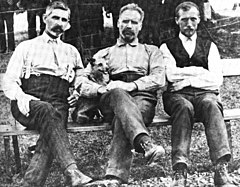 Old photograph depicting three bearded men seated outdoors on a bench with the man in the center holding a small dog