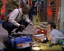 A man wearing a white shirt and blank pants kneels and speaks to a man in a blue shirt who is pinned between a subway train car and a platform. Emergency equipment lies in front of them, while the obscured figures of firefighters and emergency personnel stand behind them.