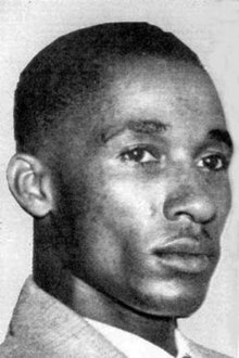 A black and white photograph of a young blank  man with short hair in tight closeup.