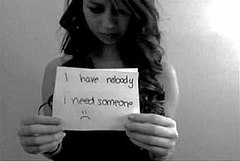 "A girl in her mid-teens holding a cut-out piece of paper or card with the words ""I have nobody, I need someone"" and a sad emoticon written on it."