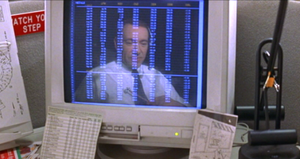 A computer monitor on a busy cubicle desk: The monitor displays a spreadsheet in seven columns which span the height of the screen. The monitor also shows the reflection of a middle-aged man in a shirt and tie, sitting close to the desk and wearing a telephone headset. The contrasts—the monitor's dark background, and the lightness of the text and the man's shirt—make the reflection more prominent between and behind the numbers.