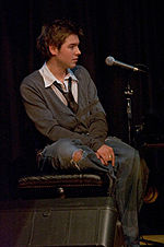 A man sits on a stool next to a microphone