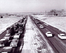 A black-and-white photo shows a four-lane freeway divided by a grass median. In the oncoming lanes, traffic is congested into the distance. With few exceptions, the freeway is surrounded by farmland.