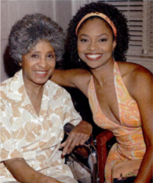 A dark-skinned woman with curly hair has her arm around an older woman in a wheelchair.