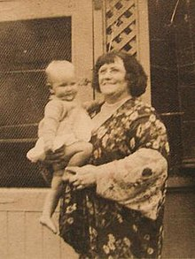 Old snapshot of Farrell. She is a plump smiling woman of 60, wearing a floral kimono and holding a toddler.