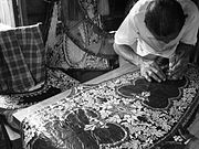 A wau-maker in his workshop. Design details in his wau are made by cutting various layers of coloured paper. The cutting is done spontaneously. Wau-maker cutting details into a wau.JPG
