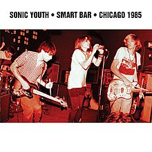 "A red hue photograph of a rock band on stage. Bold black text above reads ""Sonic Youth Smart Bar Chicago 1985."""