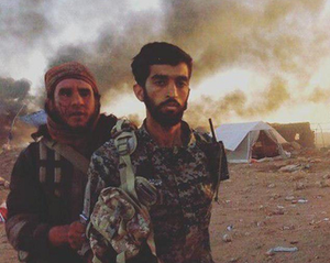 """Mohsen Hojaji - The photo that made Hojaji famous. He stoically looks at the camera while an """"anxious"""" ISIS executioner is holding him with a knife at hand. The tent and the smokes in the background as well as the beheading resemble the scene at the aftermath of the Battle of Karbala, a key event in Shia history."""