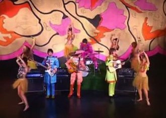 "Hello, Goodbye - The first of the three promotional clips for ""Hello, Goodbye"", showing the Beatles in their Sgt. Pepper uniforms, accompanied by female hula dancers"