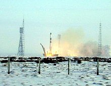 Picture of a rocket launch. The ground near the launch pad is covered in snow.