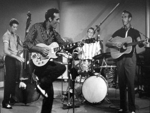 "Jamboree (1957 film) - Carl Perkins (second from left) performing ""Glad All Over"" with (left to right) Clayton Perkins, W.S. ""Fluke"" Holland, and Jay Perkins"