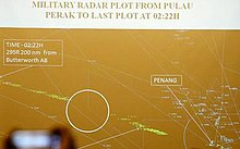 "Brown background with white lines, dots, and labels depicting air routes, waypoints, and airports. Label in the top of the image reads: ""Military radar plot from Pulau Perak to last plot at 02:22H."" Green specks form a trail from bottom centre to left centre that was Flight 370. As the caption explains, the path is in two parts, with a white circle around the blank area between them and appears to highlight a section where the aircraft was not tracked by radar. Label at left end of flight path reads: ""Time-02:22H 295R 200nm from Butterworth AB"""