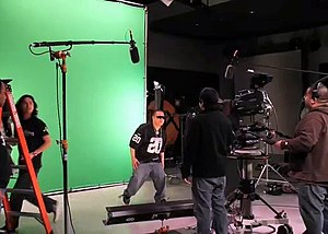 Chroma key - A live broadcast of Myx TV using green-screen chroma key. Note the lack of shadows on the screen. The whiter area near the center of the image is due to the angle this photo was taken from, and would not appear from the video camera's angle.
