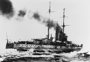 A large battleship steaming away through the water at high speed. Its stern can be seen in the foreground with water hitting the sides of the ship. Smoke can be seen billowing out of the funnels of the ship.