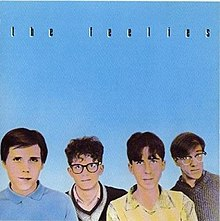 "Pastel pictures of The Feelies' faces on a blue background with ""THE FEELIES"" written in black above them"