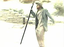 Still film image showing a bearded man wearing a jacket, shirt, and pants bulging at the thighs, with apparently normal leather shoes, carrying a walking staff