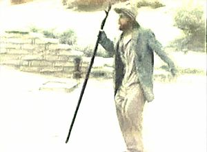 Manos: The Hands of Fate - Still film image showing Torgo wearing a jacket, shirt, and pants bulging at the thighs, carrying a walking staff. The character of Torgo was intended to be a satyr and actor John Reynolds unintentionally wore the metal rigging backward under his trousers.