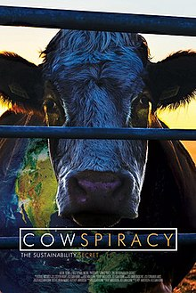 A movie poster showing a cow with a sunset in the background