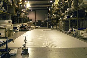 Heat sealer - Heat-sealed material lies on a warehouse floor. Notice the corded heat sealer to the left.
