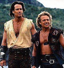Two men, the one on the left has long brown hair and is taller than the one on the right. The man on the right has long blond hair and is wearing a tunic top and leather trousers and a gauntlet on his right arm. The man on the right is wearing a waistcoat, leather trousers and a medallion around his neck.
