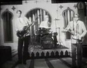 "In Bloom - Nirvana parodying early 1960s variety shows in the second ""In Bloom"" video. The band members are dressed as ""thoroughly alright and decent fellas"" and are filmed entirely in black and white."