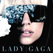 "Gaga's face wearing black glasses, whose right side is covered by blue crystals. On the bottom of the left side of the glasses, the word ""The Fame"" is inscribed in white."