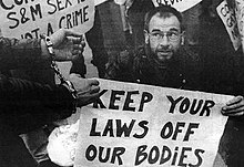 "Image shows a man holding a sign reading ""Keep Your Laws Off Our Bodies"", while another man wears a set of handcuffs"