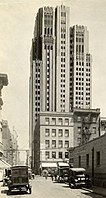 A monochrome photograph of a street in San Francisco showing automobiles from the 1920s, and a skyscraper standing tall behind smaller buildings.
