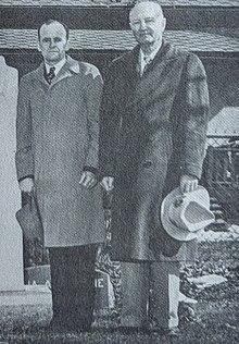 Two middle-aged men stand side-by-side wearing overcoats and holding their hats in their hands