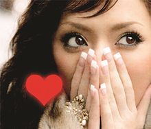 An up-close shot of Ayumi Hamasaki smiling and looking into the camera. On the lower left is a red heart.