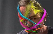 A digitally rendered version of Chris Landreth's face, slightly tilted downward, on a dark grey background. Ribbons of various colours wrap around his head in various orientations.