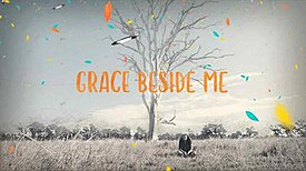 "An greyscale long shot of a young girl sitting in a grassy field next to a tree without leaves. The words ""Grace Beside Me"" are in the foreground in orange lettering, along with superimposed images of colourful leaves."