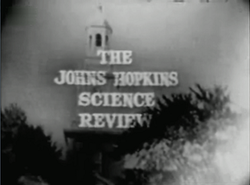 "Television screenshot looking up at the bell tower of a building through tall trees. The  words ""The Johns Hopkins Science Review"" are superposed on the image."