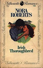 "The center of the cover shows the head and torso of a woman with long hair, leaning against the head and torso of a man. The man's right hand cups her neck, and the couple are looking at each other. In the background are a horse and a large building. Above the image are the words ""Nora Roberts"" and ""Irish Thoroughbred"". The outer edges of the cover have a solid border, with the words ""Silhouette Romance"" repeated. In the top right corner is the number 81."