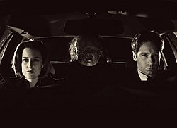 Two people are sitting in a car with a grotesque figure in the backseat. The scene is entirely in black and white footage.