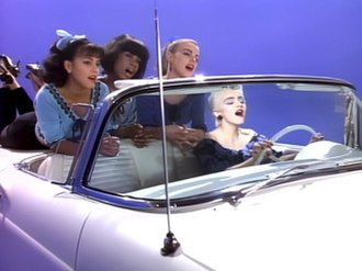 """True Blue (Madonna song) - Madonna sporting a blond bouffant short haircut, drives a 1957 Ford Thunderbird convertible with her girlfriends in the back, in the 50s inspired blue themed video for """"True Blue"""""""