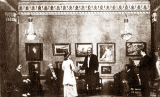 Scene from a play, with young woman standing in a smart drawing room addressing several seated men