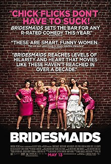 Against a red brick wall stand 6 women, 5 are wearing pink bridesmaids dresses, and one is wearing a white wedding dress