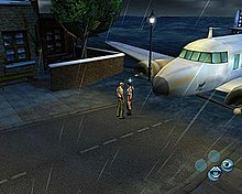 A screenshot of two people, a man and a woman, standing in front of an aeroplane; there are four circles in the lower right of the screen in a trapezoidal pattern, with a mouth in the lowest and an eye in the right-hand one