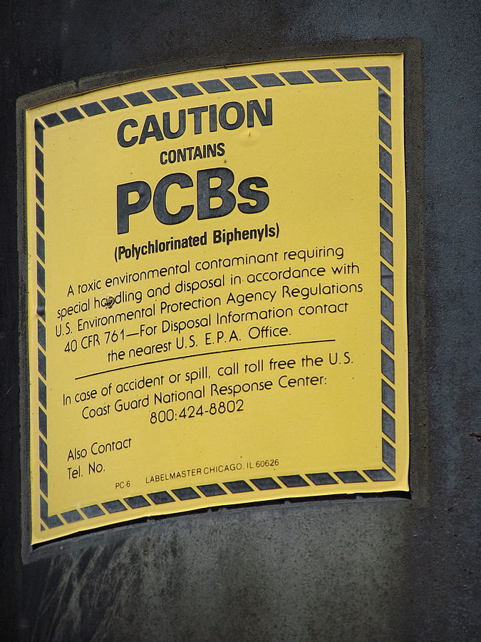 PCB warning label affixed to a railroad signal power supply transformer dating from the 1930s