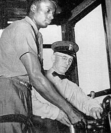 A black PTC employee is receiving instruction as a trolley operator