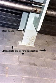 Steel beam through-penetration with incomplete fireproofing.