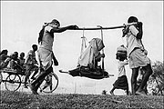 Two Muslim men (in a rural refugee train headed towards Pakistan) carrying an old woman in a makeshift doli or palanquin. 1947.