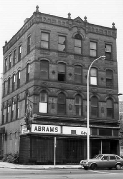 "A black-and-white photograph of a four-story building with a flat ornamented roofline seen from across a city street and slightly to its right. On the ground floor storefront the word ""Abrams"" is prominent on the building's left."