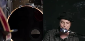 Not Over You - A screen capture from the four-minute music video, where DeGraw is pictured on the right singing the song emotionally into a microphone while playing the piano with a band, and the band's drum is pictured on the left.