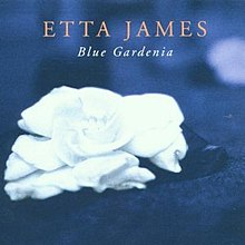 "A white gardenia flower with a blue background; above the flower is the text ""Etta James"" with ""Blue Gardenia"" below"