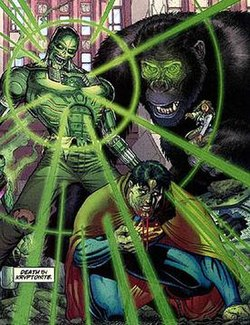 A robotic man with a green glow coming from his chest. Superman on his knees, sick and bleeing. A huge gorilla stands in the background.